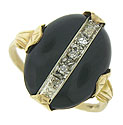 This handsome estate ring is set with an oval cut onyx adorned with a bold ribbon of white gold