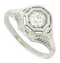 The octagonal central mounting of this antique engagement ring is set with a breathtaking round cut diamond