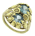 Magnificent golden cutwork leaves and flowers caress a pair of ice blue zircon on the face of this fantastic estate ring