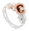 A single rose crafted of red gold and holding a sparkling diamond is the focal point of this 14K white gold antique style floral wedding band