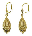 These spectacular 14K yellow gold antique drop earrings feature layers of intricate abstract floral engraving framing a faceted teardrop center