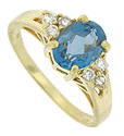 A radiant, oval cut blue topaz is set into the face of this handsome 14K yellow gold estate ring