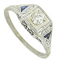 A dazzling .12 carat, H color, Vs2 clarity diamond is set into the face of this elegant 18K white gold engagement ring