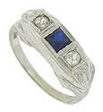 A pair of round cut diamonds frame the square cut sapphire in the center of this unique 14K white gold antique wedding band