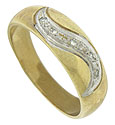 A broad curling stroke of white gold set with diamonds presses into the surface of this 14K yellow gold wedding band