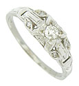 This handsome, floral inspired, 14K white gold engagement ring is set with a dazzling round cut diamond
