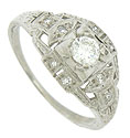 Layers of abstract geometric cutwork surround a dazzling .24 carat, D color, Si2 clarity round cut diamond on this antique engagement ring