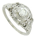 Layers of intricate filigree, abstract organic cutwork and intricate engraving adorn the surface of this magnificent Art Deco engagement ring