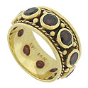 Ten bezel set garnets burst from the center of this handsome 14K yellow gold estate ring