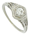Intricate organic filigree and engraving adorn the sides and shoulders of this antique 14K white gold engagement ring