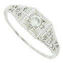 The face of this bold antique style engagement ring is subtly elevated and engraved with abstract organic decoration