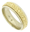 Exquisite floral engraving covers the surface of this 14K bi-color wedding band