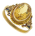Curling filigree and bold milgrain decorations frame the glowing oval citrine at the center of this romantic estate ring