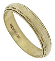 Abstract engraving and delicate milgrain decoration adorn the edges of this antique 14K yellow gold wedding band