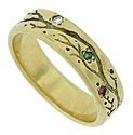 This distinctive 14K yellow gold estate wedding band features a deeply engraved vine set with a trio of stones