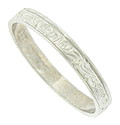 A spinning ribbon of deeply engraved abstract organic figures covers the face of this antique style wedding band