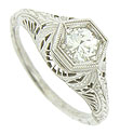 Bold organic cutwork, filigree and rich engraving adorn the sides and shoulders of this antique style engagement ring