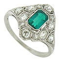 Abstract diamond frosted floral cutwork surrounds a spectacular Columbian emerald in this breathtaking antique engagement ring