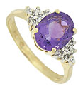 A violet hued oval cut amethyst is the star of this elegant 14K yellow gold estate ring