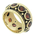 Bezel set garnets burst from the center of this handsome 14K yellow gold estate ring
