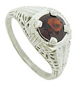 This captivating antique style ring features a .38 carat, deep red garnet at its center
