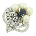 Luminous pearls, fine faceted diamonds and deep blue sapphire form a breathtaking flower on the surface of this elegant estate ring