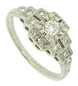 This exquisite antique engagement ring features abstract floral cutwork frosted with fine faceted diamonds
