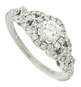 A stunning .42 carat, G color, Si1 clarity round cut diamond glows from the center of this dazzling antique style engagement ring