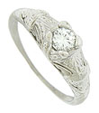 Intricate abstract organic engraving adorns the surface of this stunning antique engagement ring