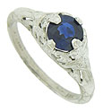 A deep blue 1.05 carat, round cut sapphire is set into the face of this elegant 14K white gold engagement ring