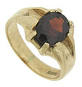 A deep red, oval cut garnet is presented at the center of this floral inspired estate ring