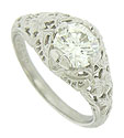 Intricately engraved organic filgree cover the sides and shoulders of this breathtaking antique style engagement ring