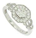 Brilliant round cut diamonds spin in circles on the face of this antique style engagement ring