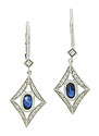 Abstract diamond figurals frame single oval cut sapphires on these estate earrings