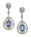 Intricate curling filigree surrounds an oval cut sapphire set into the tear shaped frame of these antique style earrings