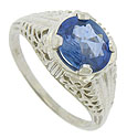 A fabulous 1.66 carat oval cut sapphire is presented in the face of this captivating Art Deco engagement ring