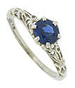 This romantic antique style engagement ring features a .85 carat deep blue sapphire