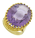 A magnificent oval cut amethyst is presented at the center of this stunning 14K yellow gold estate ring