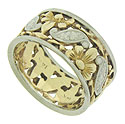Jaunty yellow gold blooms and spinning leaves of white gold dance across the face of this exquisite 14K bi-color wedding band