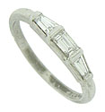 A trio of brilliant, baguette cut diamonds press into the face of this estate wedding band