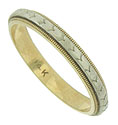 A spinning white gold ribbon of abstract leaves presses into a band of yellow gold to create this vintage wedding ring