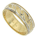 Sparkling jewel cut engraving on the face of this yellow gold wedding band reveals a dazzling white gold interior
