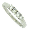 A quartet of dazzling round cut diamonds adorn the face of this handsome vintage wedding band
