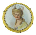 This hand painted porcelain pin features a beautiful socialite adorned in pale yellow and wearing a hat of curling feathers