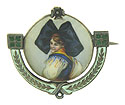 This fashion plate antique portrait pin features a detailed female, adorned with colorful dress and large hair bow