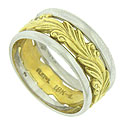 Bold, deeply engraved leafy vines curl across the face of this antique style wedding band