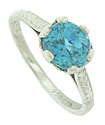 A spectacular round cut blue zircon glows from the face of this stunning estate ring