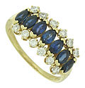 A string of marquis cut sapphires edged in dazzling round cut diamonds are set in the face of this elegant estate ring