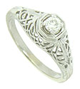 A lacy web of delicate filigree surrounds a sparkling .20 carat, H color, Si1 clarity diamond at  the center of this antique style engagement ring