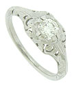 Intricate abstract cutwork decorates the surface of this antique style engagement ring